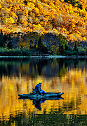 Man fishing from a kyak in Profile Lake, New Hampshire, USA.
