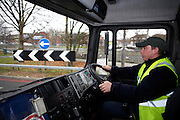Wearing a high-vis tabard and peaked cap, a young driver sits at the wheel of his HGV lorry on the A3 trunk road in London