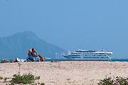Two men relax in beach chairs as a cruise ship passes in front of Diamond Head.