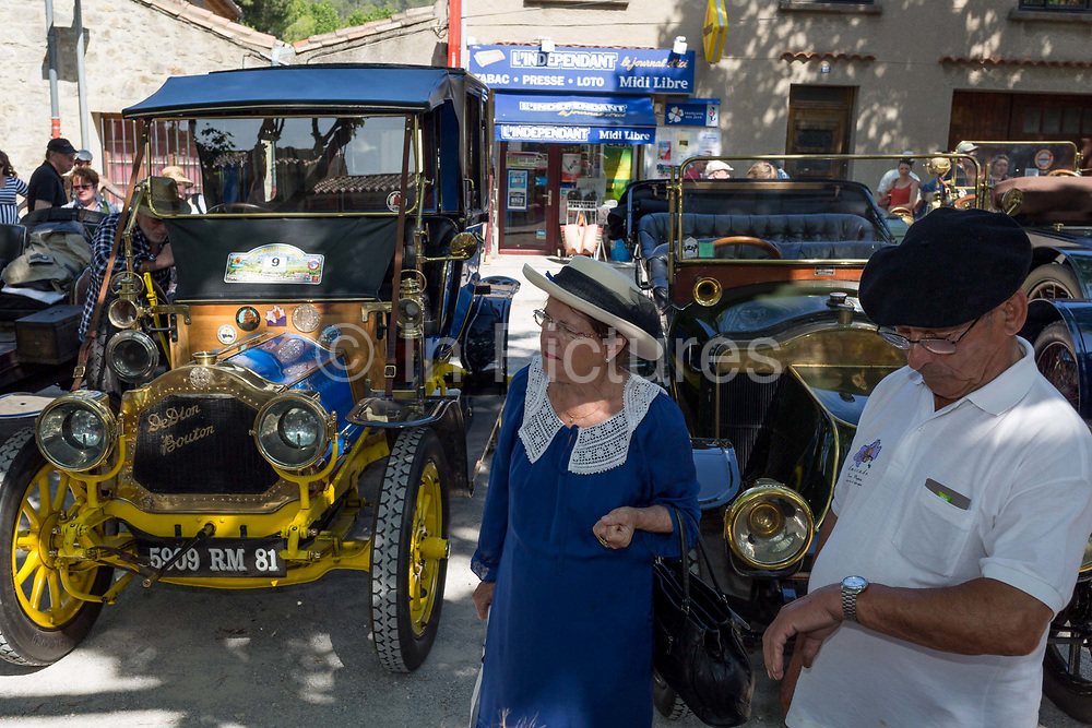 An elderly French couple and visiting vintage cars in a rural village, during a three-day rally journey through the Corbieres wine region, on 26th May, 2017, in Lagrasse, Languedoc-Rousillon, south of France. Lagrasse is listed as one of Frances most beautiful villages and lies on the famous Route 20 wine route in the Basses-Corbieres region dating to the 13th century.