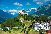 Tarasp Castle surrounded by larch and pine forest in the Lower Engadine Valley, Switzerland