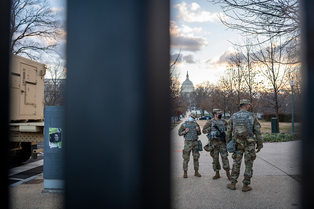Washington DC, USA - January 18, 2021: National Guard soldiers stand behind the recently constructed fence surrounding the U.S. Capitol.