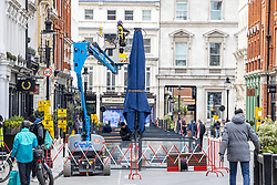 © Licensed to London News Pictures. 07/04/2021. London, UK. With less than 5 days before the great unlock-down, crane operators are in full swing preparing large umbrellas in the outdoor seating areas of restaurants in Covent Garden, London. This week Prime Minister, Boris Johnson announced that pubs, shops, gyms and hairdressers will be allowed to open to the public from this Monday, 12th April 2021 as England takes its first big steps out of the coronavirus pandemic restrictions. Photo credit: Alex Lentati/LNP