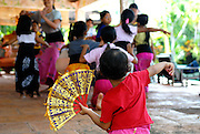 Young girl (2 years old) watching and copying older children at traditional Balinese dance school. Sanur, Bali, Indonesia.
