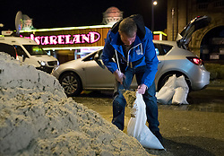 © Licensed to London News Pictures. 13/01/2017. Great Yarmouth, UK. A resident fills sandbanks on the seafront in Great Yarmouth. The Environment Agency has warned residents to prepare for evacuation as as they fear flooding at tonight's high tide. Photo credit: Peter Macdiarmid/LNP