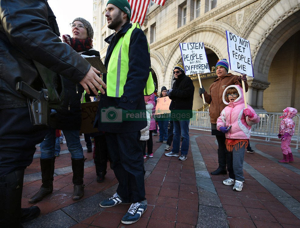 """December 10, 2016 - Washington, DC, USA - Security talks with organizers about march around Trump hotel. Children's Rally for Kindness takes place at Trump International Hotel in Washington DC on December 10, 2016 organized by the Takoma Parents Action Coalition.  According to their FaceBook page, it was a call to President-elect Donald Trump: ''to remember these lessons as he prepares to take office and implement policies that will affect the lives of children and families across our diverse nation.''.''All over the world, across cultures and countries, children learn the same basic lessons: .Ã'be kind,Ã"""" .Ã'tell the truth,Ã"""" .Ã'be fair,Ã"""" .Ã'respect everyone,Ã"""" .Ã'treat others the way you want to be treated,Ã"""" .Ã'donÃ•t touch others if they donÃ•t want to be touched. (Credit Image: © Carol Guzy via ZUMA Wire)"""