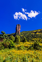 """A rock formation called """"The Devils Nose (or Tikil Dingay)"""", with mustard flowers in foreground, near Gondar, Ethiopia."""