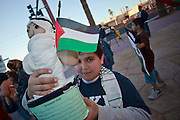 """30 DECEMBER 2008 -- PHOENIX, AZ: A Palestinian boy holds up his """"Ancestor Doll,"""" a school project, during a pro-Palestinian protest in Phoenix Tuesday. About 200 people from a variety of human rights and peace activists organizations in Phoenix, AZ, marched in opposition to the Israeli attacks on Gaza and in favor of Palestinian rights on Tuesday, the fourth day of Israeli air strikes on Hamas facilities in Gaza. Photo by Jack Kurtz / ZUMA Press"""