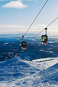 Vi från Åreskutan ner mot dalgången en solig eftermiddag. Skidåkare på väg ner i backarna och skidåkare på väg upp i Gondolen.