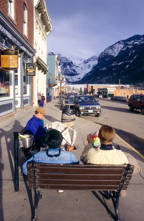 People enjoy the warm afternoon sun in Telluride as a snow squall gathers over Telluride Peak.