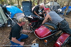 Tim Taylor and Charlie Anderson help their riding buddy Billy Mitchell do maintenance on his bike in their campground by the Cabbage Patch before the return ride of 4,600 miles to Washington state. Daytona Bike Week. FL, USA. March 12, 2014.  Photography ©2014 Michael Lichter.
