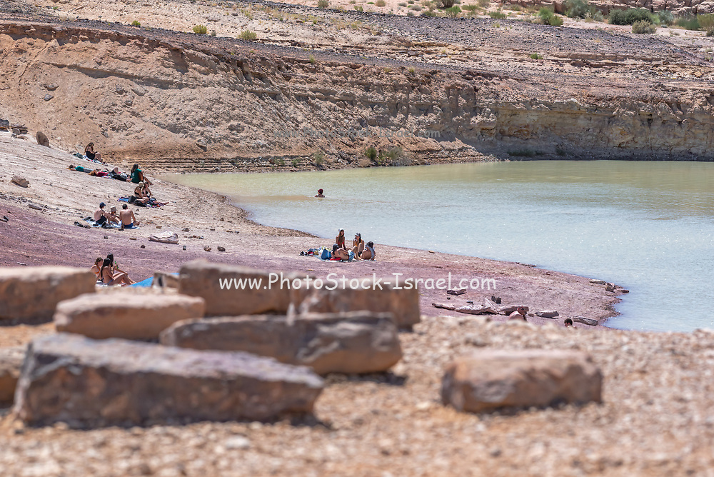 Hikers swim at a natural water hole off the beaten track in the Negev Desert, Israel
