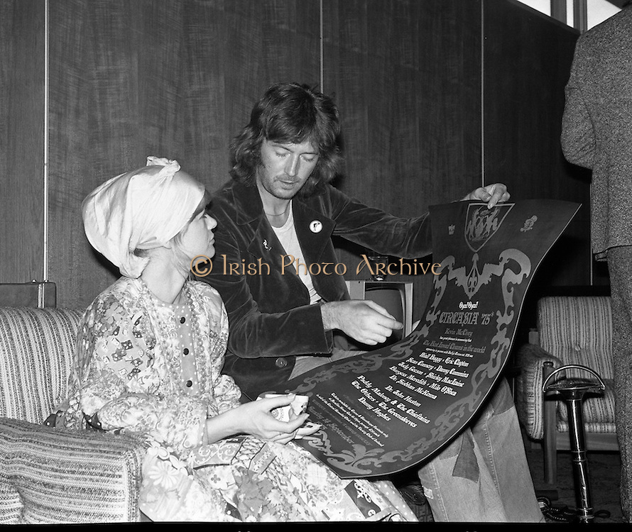 """Arrivals of Eric Clapton and Judy Geeson at DAP..1975..13.09.1975..09.13.1975..13th September 1975..Today saw the arrivals of musician Eric Clapton and actress Judy Geeson at Dublin Airport. They are in Ireland to take part in """"Circasia 75"""" at Straffan House,Co Kildare..Image shows Judy Geeson and Eric Clapton viewing the poster ,with a spectacular cast list,for """"Circasia 75' while relaxing in the VIP lounge in Dublin Airport."""