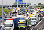 Heavy goods vehicles trucks in traffic congestion on M25 motorway, London, United Kingdom