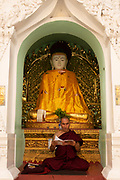 Monk reading Buddhist writings in one of the small temples in the Shwedagon Pagoda complex, Yangon (Rangoon), It is the most sacred Buddhist stupa in Myanmar and one of the most important religious reliquary monuments in the world