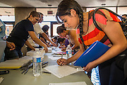"""25 AUGUST 2012 - PHOENIX, AZ:   Immigrants sign into the deferred action workshop Saturday. Hundreds of people lined up at Central High School in Phoenix to complete their paperwork to apply for """"Deferred Action"""" status under the Deferred Action for Childhood Arrivals (DACA) program announced by President Obama in June. Volunteers and lawyers specialized in immigration law helped the immigrants complete the required paperwork. Under the program, the children of undocumented immigrants brought to the US before they turned 16 years old would not be subject to deportation if they meet a predetermined set of conditions.   PHOTO BY JACK KURTZ"""