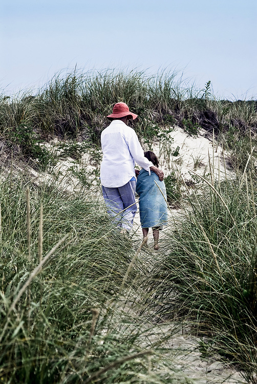 Girl wrapped in a beach towel walking through dune grass with her grandmother, Brewster, Cape Cod, MA.