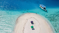 Aerial view of a sandbank, North Malé Atoll, Maldives, Indian Ocean with an anchored dhoni, boat and people swimmimg, sunbathing