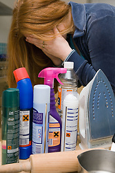 Upset woman surrounded by a selection of household products used for domestic abuse,
