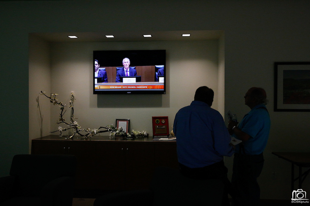 Warren Wettenstein, left, and Isaac Stringer watch Rob Means discuss his goals for City Council from the lobby during the Milpitas City Council Forum at Milpitas City Hall in Milpitas, California, on October 9, 2014. (Stan Olszewski/SOSKIphoto)