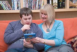 Mother and teenage son with Downs Syndrome reading a DVD cover,