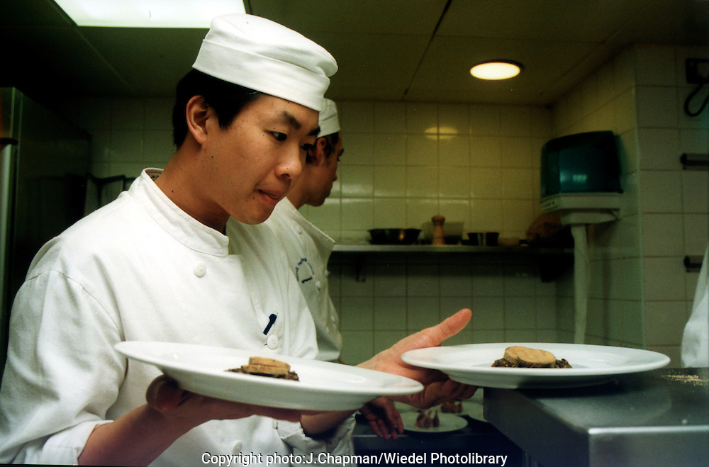Young oriental chef working in a kitchen of a restaurant.
