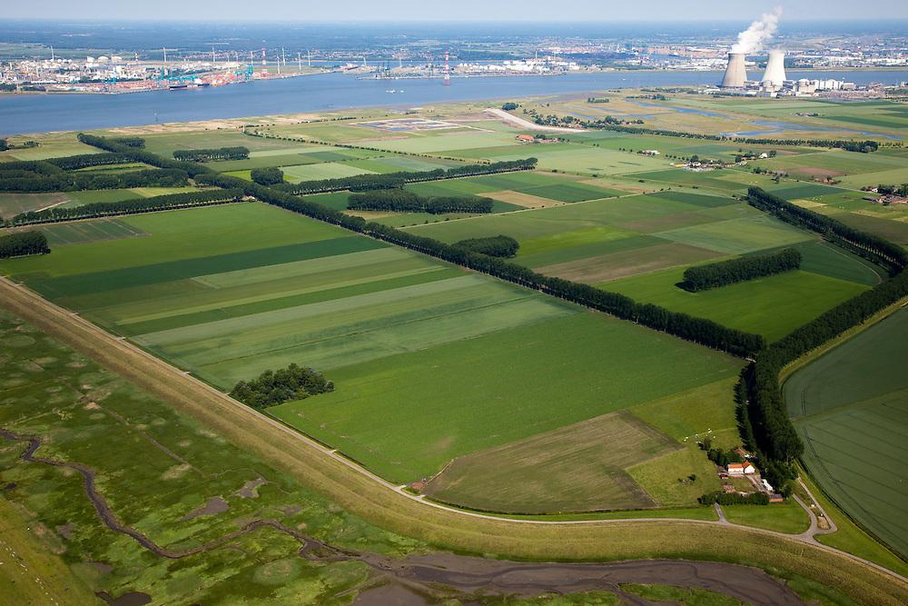 Nederland, Zeeland, Zeeuws-Vlaanderen, 12-06-2009; Hertogin Hedwigepolder met Verdronken Land van Saeftinghe in de voorgrond, kerncentrale van Doel (Belgie) aan de horizon. In verband met de komende verdieping van de vaargeul van de nabijgelegen Westerschelde (links) moet er volgens de Europese habitatrichtlijn natuurcompensatie komen. Door de polder en de Belgische Prosperpolder, aan de andere kant van de grens (gemarkeerd door de dunne lijn bomen) te ontpolderen wordt er grond terug gegeven aan de natuur, zogenaamde natuurcompensatie (advies commissie onder leiding van Ed Nijpels). De maatregelen zijn omstreden, in het Belgisch deel van het gebied is men reeds begonnen..Hertogin Hedwigepolder with Drowned Land of Saeftinghe in the foreground, nuclear plant Doel (Belgium) at the horizon. Because of the future enlargement of the fairway of the nearby Westerschelde (on the left) , the nature has to be compensated (according to the European Habitats Directive). The Hertogin Hedwige polder (and the adjacent Belgian polder - on the other side of the border - the Prosperpolder) are to be given back to nature, i.e. are to be 'de-polderd'. The measures are controversial, but in the Belgian part of the polders works have already been started.Swart collectie, luchtfoto (25 procent toeslag); Swart Collection, aerial photo (additional fee required).foto Siebe Swart / photo Siebe Swart