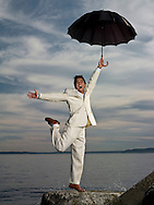Asian man in suit with umbrella, in front of Elliott Bay, WA, USA.