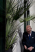 A businessman checks his messages beneath the shadows of a potted plant outside an Itsu shop in the Square Mile, the capitals financial district, on 3rd March 2017, in the City of London, England.