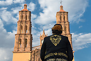 A female mariachi performer stands in front of the Parroquia Nuestra Señora de Dolores Catholic Church also called the Church of our Lady of Sorrows at the Plaza Principal in Dolores Hidalgo, Guanajuato, Mexico. Miguel Hildago was a parish priest who issued the now world famous Grito - a call to arms for Mexican independence from Spain.