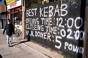 The handwritten capital letters proclaiming the best kebabs and the business's opening times on the Commercial Road in the East End, on 21st October 2021, in London, England.