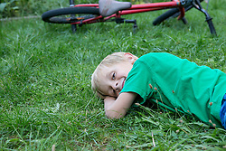 Smiling young boy lying on a meadow