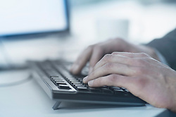 Cropped image of business person typing on computer keyboard, Freiburg im Breisgau, Baden-Wuerttemberg, Germany