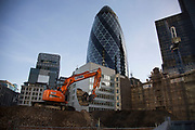 Construction site in the City of London in the shadow of the Gherkin, UK. A digger excavates the ground to prepare the area for another high rise building.