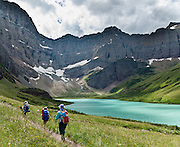 """Hike to Cracker Lake 11.2 miles round trip (with 1140 feet gain) beneath soaring peaks of the Lewis Range in Glacier National Park, Montana, USA. See the small and rapidly melting Siyeh Glacier clinging to the rock wall at the head of Cracker Lake. Of the 150 glaciers existing in Glacier NP in the mid 1800s, only 25 active glaciers remain as of 2010, and all may disappear as soon as 2020, say climate scientists. Glaciers carved spectacular U-shaped valleys and pyramidal peaks here as recently as the Last Glacial Maximum (the last """"Ice Age"""" 25,000 to 13,000 years ago). An overwhelming consensus of world scientists agree that global warming is indeed happening and humans are contributing to it through emission of heat-trapping """"greenhouse gases,"""" primarily carbon dioxide (see www.ucsusa.org). Since the industrial revolution began, humans have increased atmospheric CO2 concentration by 35% (through burning of fossil fuels, deforesting land, and grazing livestock). Since 1932, Canada and USA have shared Waterton-Glacier International Peace Park, which UNESCO declared a World Heritage Site (1995) containing two Biosphere Reserves (1976). Rocks in the park are primarily sedimentary layers deposited in shallow seas over 1.6 billion to 800 million years ago. During the tectonic formation of the Rocky Mountains 170 million years ago, the Lewis Overthrust displaced these old rocks over newer Cretaceous age rocks."""