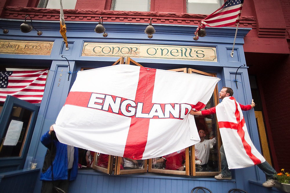 Michael Leaves (right), who owns the local soccer shop Rocky Mountain Soccer, hangs a large English flag outside Conor O'Neill's pub in Boulder, Colorado during the World Cup match between England and the USA on June 12, 2010. The match ended in a 1-1 tie.