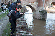 Young boys fishing along the Tarn River in Albi, Southern France. With his fishing rod bending, this boy had caught something way bigger than he had planned for and was struggling to land a 2 metre long catfish.