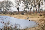 Nederland, Ooij, 17-2-2019De bizonbaai is een voormalig zandwingat, recreatieplas, waterplas, meertje, baai, langs de rivier de Waal. Onderdeel van staatsbosbeheer. Vanwege het mooie weer op deze warmste 17 februari ooit trekken veel mensen, dagjesmensen, fietsers, er op uit om te genieten van het mooie weer .Op de zomerdijk staan grote hoge bomen. De bisonbaai is onderdeel van de wandelroute, pelgrimsroute, walk of wisdom door het rijk van Nijmegen.Foto: Flip Franssen
