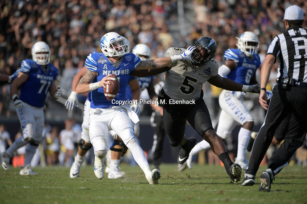 Memphis quarterback Riley Ferguson (4) scrambles away from Central Florida defensive lineman Jamiyus Pittman (5) during the second half of the American Athletic Conference championship NCAA college football game Saturday, Dec. 2, 2017, in Orlando, Fla. Central Florida won 62-55. (Photo by Phelan M. Ebenhack)