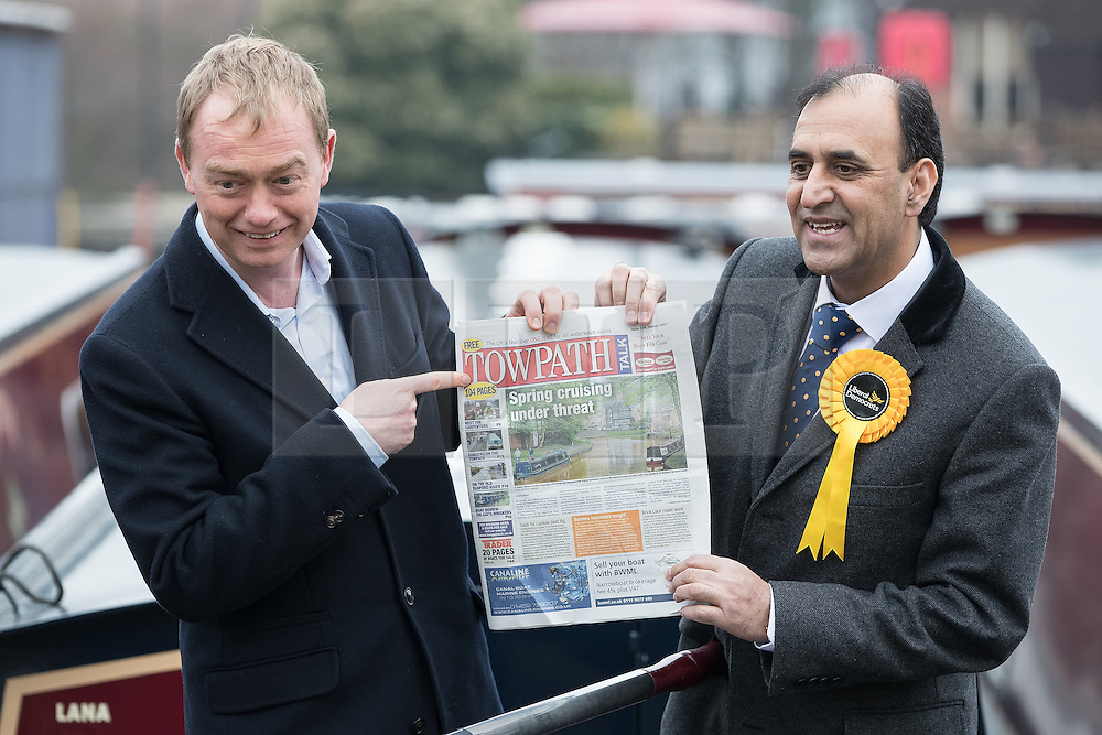 """© Licensed to London News Pictures . 14/02/2017 . Stoke-on-Trent , UK . Lib Dem leader TIM FARRON joins candidate DR ZULFIQAR ALI , pictured holding a copy of Towpath Talk (headline """" Spring cruising under threat """" ), whilst campaigning at Festival Park Marina in Etruria , in the Stoke Central by-election . Photo credit : Joel Goodman/LNP"""