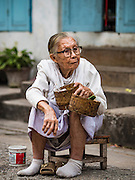 """12 MARCH 2016 - LUANG PRABANG, LAOS: A Lao woman waits to give alms to Buddhist monks during the morning tak bat in Luang Prabang. Luang Prabang was named a UNESCO World Heritage Site in 1995. The move saved the city's colonial architecture but the explosion of mass tourism has taken a toll on the city's soul. According to one recent study, a small plot of land that sold for $8,000 three years ago now goes for $120,000. Many longtime residents are selling their homes and moving to small developments around the city. The old homes are then converted to guesthouses, restaurants and spas. The city is famous for the morning """"tak bat,"""" or monks' morning alms rounds. Every morning hundreds of Buddhist monks come out before dawn and walk in a silent procession through the city accepting alms from residents. Now, most of the people presenting alms to the monks are tourists, since so many Lao people have moved outside of the city center. About 50,000 people are thought to live in the Luang Prabang area, the city received more than 530,000 tourists in 2014.       PHOTO BY JACK KURTZ"""