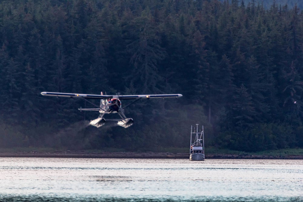 A small floatplane takes off from Swanson Harbor, Southeast Alaska.  Leaving a fishing boat in its wake.