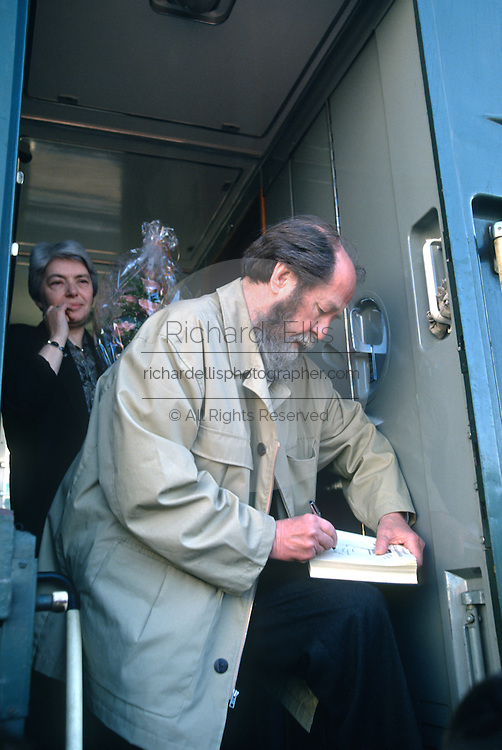 Russian Nobel prize novelist Alexander Solzhenitsyn signs a copy of his book after arriving by train returning to his homeland as his wife Alya Svetlova looks on June 5, 1994 in Khabarovsk, Russia. Solzhenitsyn was expelled from the Soviet Union in 1974 but returned after the fall of the Soviet Union.