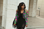 A woman in a beaded jacket poses for photos outside the fashion show.