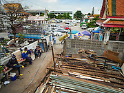 12 NOVEMBER 2015 - BANGKOK, THAILAND:  Demolition workers take a break while tearing down a home at Wat Kalayanmit. Fifty-four homes around Wat Kalayanamit, a historic Buddhist temple on the Chao Phraya River in the Thonburi section of Bangkok, are being razed and the residents evicted to make way for new development at the temple. The abbot of the temple said he was evicting the residents, who have lived on the temple grounds for generations, because their homes are unsafe and because he wants to improve the temple grounds. The evictions are a part of a Bangkok trend, especially along the Chao Phraya River and BTS light rail lines. Low income people are being evicted from their long time homes to make way for urban renewal.       PHOTO BY JACK KURTZ