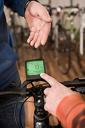 Man explaining tachometer in bike shop