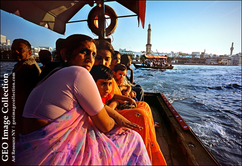 """Indian families join the rush hour procession of water taxis, called """"abras"""" in Arabic, crossing Dubai Creek, a traditional seaport crowded with wooden ships, or dhows, that trade with Iraq, Iran, Yemen, Somalia, and India. Some 80 percent of Dubai's residents are expatriates, including numerous South Asian blue-collar and professional workers."""