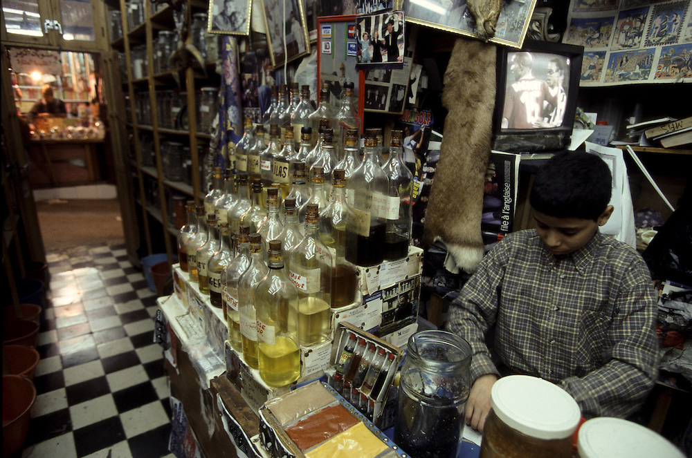 Boy selling traditional pharmaceutical products as roots and herbs in a shop inside Fez Medina.