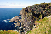 South west cliffs, Handa Island, looking west, with walker, and seabird nesting ledges on cliff, Sutherland, Highland.