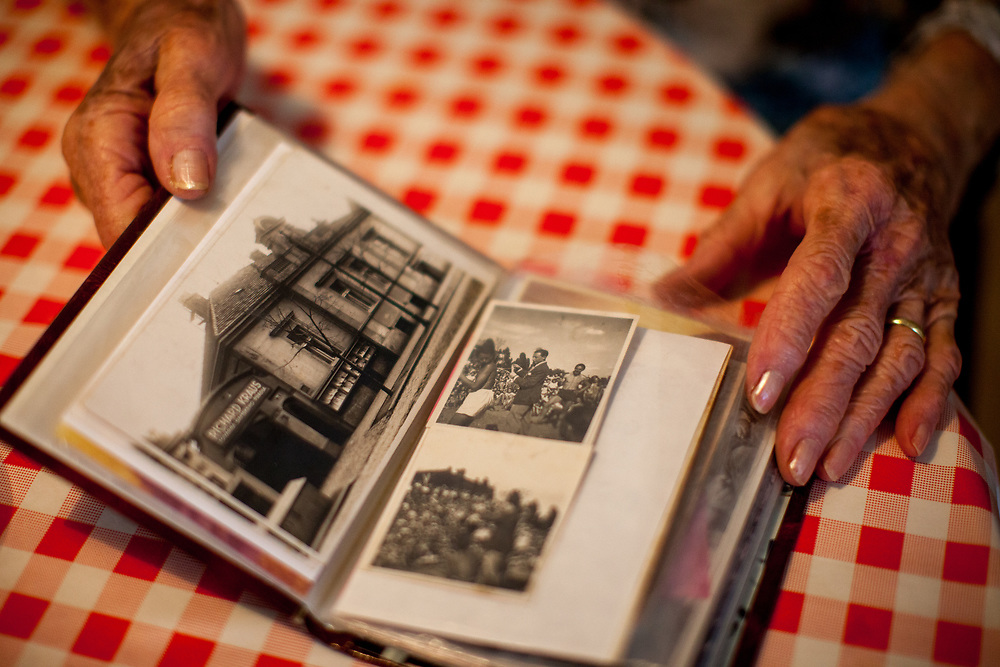 """Dita Kraus with a photo album from the past (the left image shows the factory building of her husbands family) in her flat in Prague Vinohrady. Born in Prague to a Jewish family in 1929, Dita Kraus has lived through the most turbulent decades of the twentieth and early twenty-first centuries. Here, Dita writes in her book """"A Delayed Life: The true story of the Librarian of Auschwitz"""" with startling clarity on the horrors and joys of a life delayed by the Holocaust. From her earliest memories and childhood friendships in Prague before the war, to the Nazi-occupation that saw her and her family sent to the Jewish ghetto at Terezín, to the unimaginable fear and bravery of her imprisonment in Auschwitz and Bergen-Belsen, and life after liberation."""